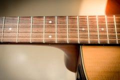 Крупный план к fingerboard акустической гитары с backgro softfocus Стоковые Фотографии RF