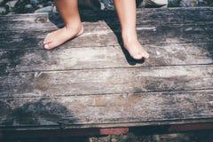 Крупный план маленькой девочки босоногий ноги на предпосылке планки Стоковые Изображения