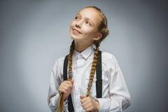 Крупный план мечтая маленькая девочка смотря вверх против серой предпосылки Стоковые Фотографии RF