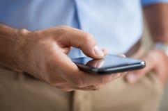 Крупный план мобильного телефона человека печатая Стоковые Изображения RF