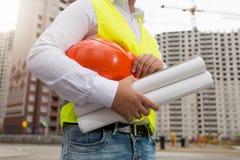 Крупный план молодого архитектора представляя с защитным шлемом и светокопиями дальше стоковое фото