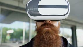 Крупный план молодого бородатого человека используя шлемофон виртуальной реальности для опыта 360 VR и взятие стекел усмехаясь ou видеоматериал