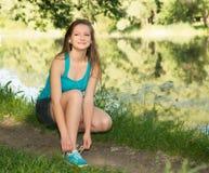Крупный план молодой женщины связывая шнурки ботинка Женский фитнес ru спорта Стоковая Фотография