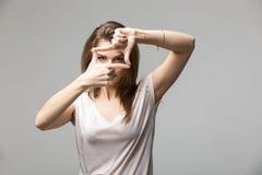 Крупный план молодой красивой женщины брюнет делая рамку с ее пальцами, над серой предпосылкой Стоковые Изображения