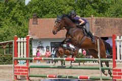 Крупный план молодой скакать horsewoman горизонтально Стоковые Фото