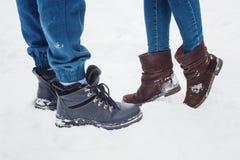 Крупный план мужских и женских ног во время даты в зиме, более короткая женщина сполз до человека достигаемости более высокоросло Стоковое Изображение RF