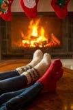 Крупный план мужских и женских ног в шерстяных носках грея на burni Стоковое Изображение RF