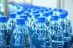 Крупный план на бутылках минеральной воды в сырцовом и линиях Стоковые Фото
