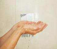 Крупный план на воде руки женщины заразительной падает в ливень Стоковое Фото