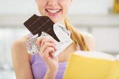 Крупный план на девушке подростка с книгой и шоколадным батончиком Стоковая Фотография RF
