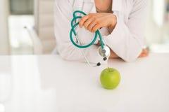 Крупный план на женщине доктора с стетоскопом и яблоком Стоковые Фото