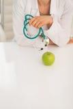 Крупный план на женщине доктора с стетоскопом и яблоком Стоковое Изображение