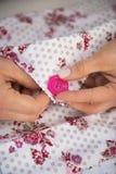 Крупный план на кнопке женщины dressmaker шить стоковая фотография