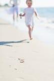 Крупный план на матери и младенце бежать вдоль берега моря стоковые фото