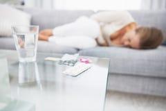 Крупный план на медицине на таблице и чувствуя плохой женщине в предпосылке Стоковые Фотографии RF