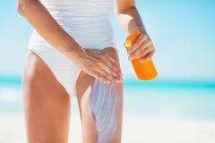 Крупный план на молодой женщине прикладывая creme блока солнца на пляже стоковая фотография rf