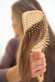 Крупный план на молодой женщине расчесывая волосы Стоковое фото RF