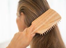 Крупный план на молодой женщине расчесывая волосы Стоковые Изображения