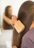Крупный план на молодой женщине расчесывая волосы Стоковые Изображения RF