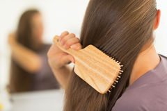Крупный план на молодой женщине расчесывая волосы Стоковая Фотография