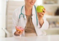 Крупный план на докторе выбирая между яблоком и донутом Стоковые Фото