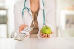Крупный план на докторе держа яблоко и деньги пакуют Стоковые Изображения