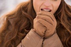 Крупный план на руках женщины грея с дышает в зиме outdoors стоковые фото