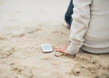Крупный план на сотовом телефоне около женщины сидя на пляже Стоковые Изображения RF