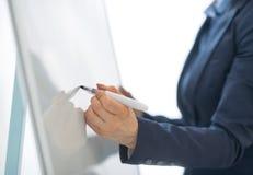 Крупный план на сочинительстве бизнес-леди на flipchart стоковая фотография