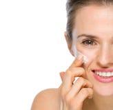 Крупный план на счастливой женщине прикладывая creme на щеке стоковые фото