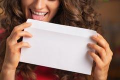 Крупный план на счастливой молодой женщине лижа конверт стоковая фотография rf