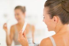 Крупный план на счастливой молодой женщине с тестом на беременность стоковое фото