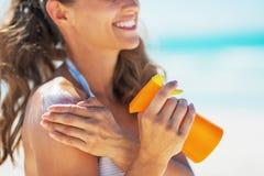 Крупный план на усмехаясь молодой женщине прикладывая creme блока солнца стоковые фотографии rf