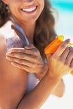 Крупный план на усмехаясь молодой женщине прикладывая creme экрана солнца стоковые фото