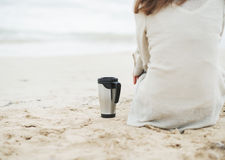 Крупный план на чашке напитка около женщины в свитере сидя на пляже Стоковые Фото