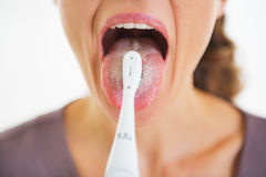 Крупный план на языке чистки женщины используя зубную щетку стоковое фото