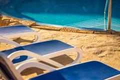 Крупный план несколько из loungers солнца красивым бассейном Стоковое Изображение RF