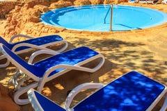 Крупный план несколько из loungers солнца красивым бассейном Стоковое Фото