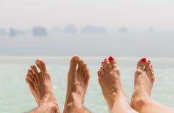 Крупный план ног пар над морем и небом на пляже Стоковая Фотография RF