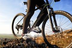 Крупный план ног человека велосипедиста ехать горный велосипед на внешнем следе на холме Стоковое Изображение