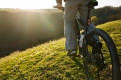Крупный план ног человека велосипедиста ехать горный велосипед на внешнем следе Стоковое фото RF