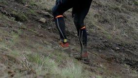 Крупный план ног людей бегунов идя гористый