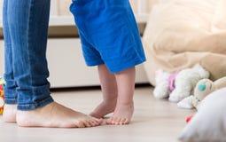 Крупный план ног ` s младенца стоя перед ногами матерей на floo стоковые фотографии rf