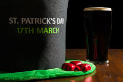 Крупный план дня St. Patrick с пинтой черных пива и шляпы сверх Стоковое фото RF