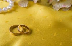 Крупный план обручальных колец на желтой скатерти Стоковая Фотография RF