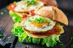 Крупный план очень вкусного бургера с салатом, беконом и яичками Стоковое Изображение RF