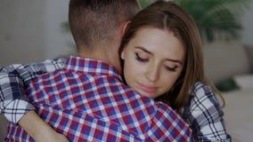 Крупный план пар осадки детенышей обнимает один другого после ссоры Женщина смотря мечтательна и уныла обнимает ее boyfrined дома сток-видео
