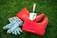 Крупный план перчаток, gumboots и лопаткоулавливателя на зеленой траве Стоковое Фото