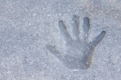Крупный план печати руки ребенка в песке грязи конкретного тротуара Стоковое Фото