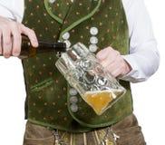 Крупный план пива баварского человека лить в стекле Стоковое фото RF